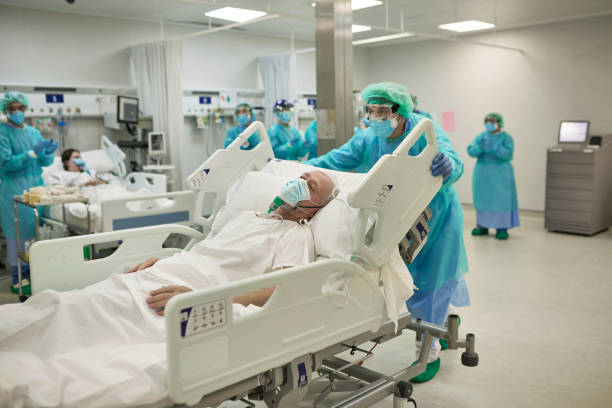 Healthcare Worker Moving COVID-19 Patient in Hospital Bed stock photo
