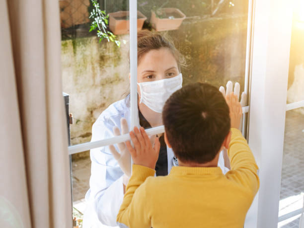 healthcare worker posing seeing her son with a window glass separating them to avoid possible contagion - hand on glass covid foto e immagini stock