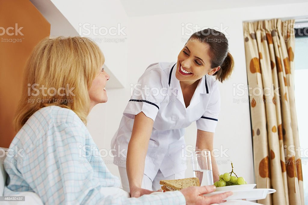 Healthcare worker serving breakfast to senior patient royalty-free stock photo
