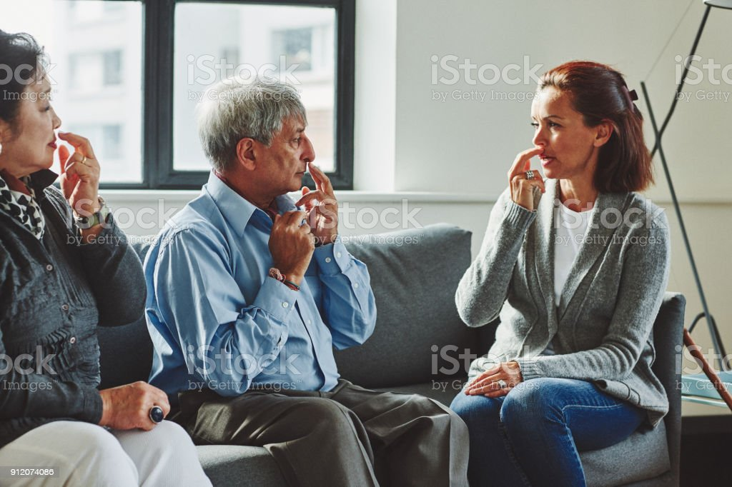 Healthcare worker showing the pressure points to senior couple stock photo