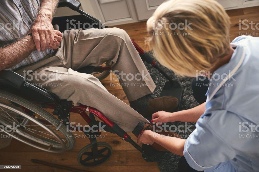 Mitarbeiter binden Schnürsenkel des behinderte ältere Menschen – Foto