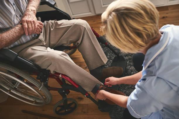 gezondheidszorg werknemer stropdas schoenkant van gehandicapte senior man - thuiszorg stockfoto's en -beelden