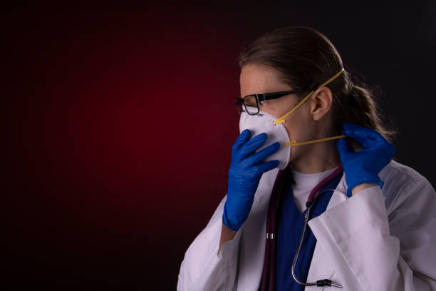 COVID-19 healthcare worker using PPE protective equipment stock photo