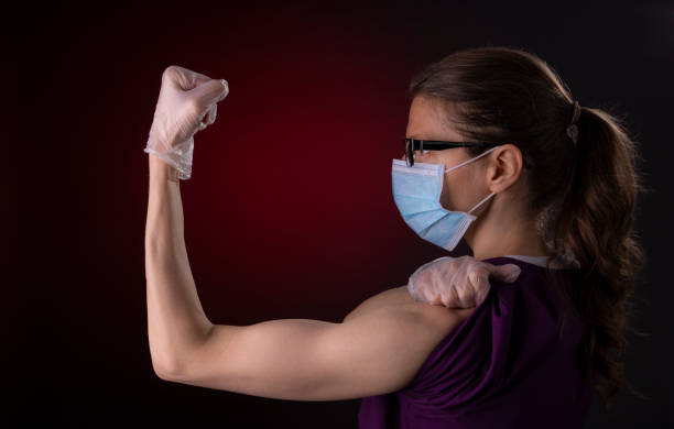 COVID-19 healthcare worker using PPE protective equipment showing strength stock photo
