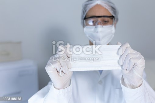 Caucasian female healthcare worker wearing a lab coat, face mask and surgical gloves against coronavirus, covid 19, presenting a face mask to camera.
