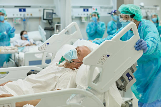 Healthcare Worker Wheeling COVID-19 Patient in Hospital Bed stock photo