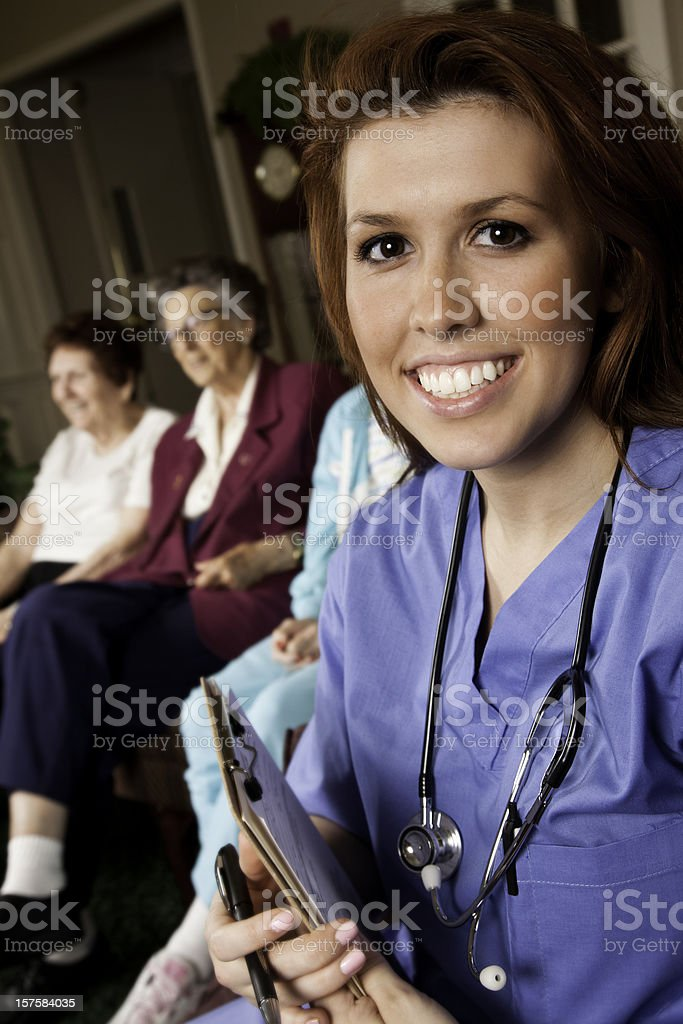 Healthcare Worker With Clipboard in Front of Senior Patients royalty-free stock photo