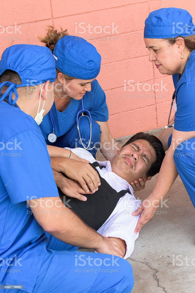 Healthcare workers helping a man in trouble stock photo