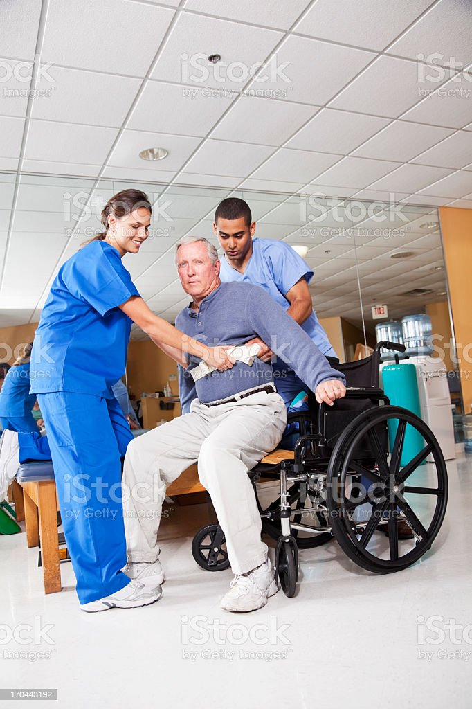 Healthcare workers helping patient into wheelchair stock photo