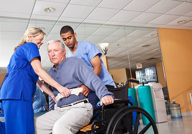 Healthcare workers helping patient into wheelchair Physical therapists helping patient (60s) from treatment table into wheelchair. retrieving stock pictures, royalty-free photos & images