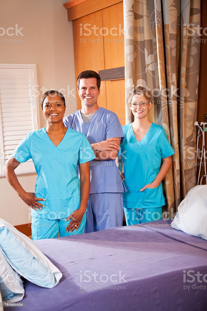 Healthcare workers in hospital room royalty-free stock photo