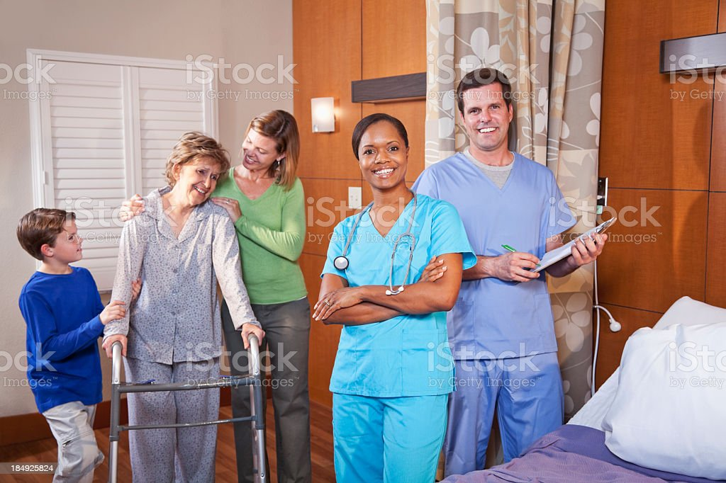 Healthcare workers in hospital room with senior patient and fami royalty-free stock photo