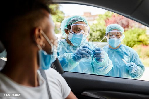 Young man sitting in car watching as hospital team in protective workwear place nasal swab specimen in sterile container.