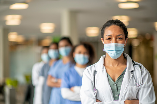 A diverse group of women stand in an institutional building in medical wear. A woman wearing scrubs stands at the forefront with a mask that is pulled down.