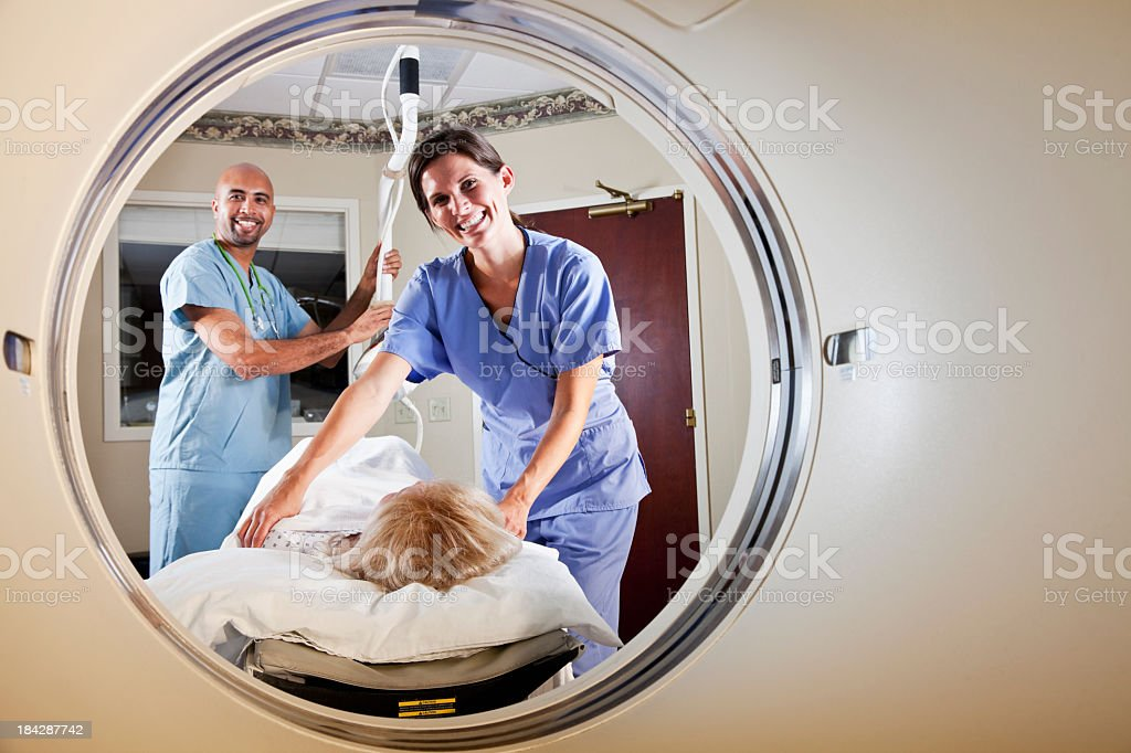 Healthcare workers preparing patient for CT scan stock photo