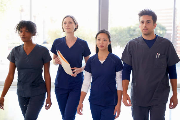 Healthcare workers walk through hospital with patient notes stock photo