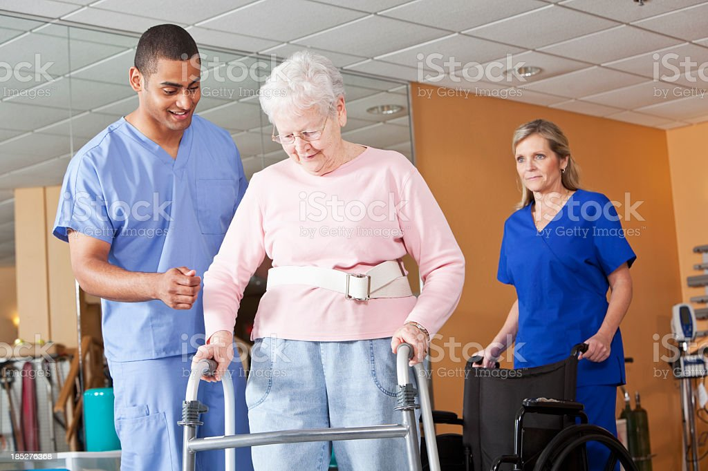 Healthcare workers with senior woman using walker royalty-free stock photo