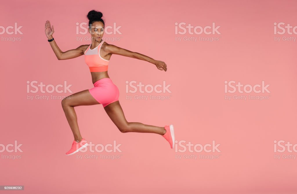Healthy african woman sprinting on pink background stock photo