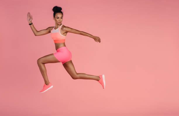gesunden afrikanerin sprinten auf rosa hintergrund - rosa training stock-fotos und bilder