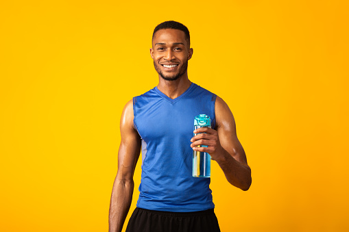 Portrait Of Athletic Black Man Holding Bottle Of Refreshing Water, Resting After Workout, Thirsty Male With A Drink