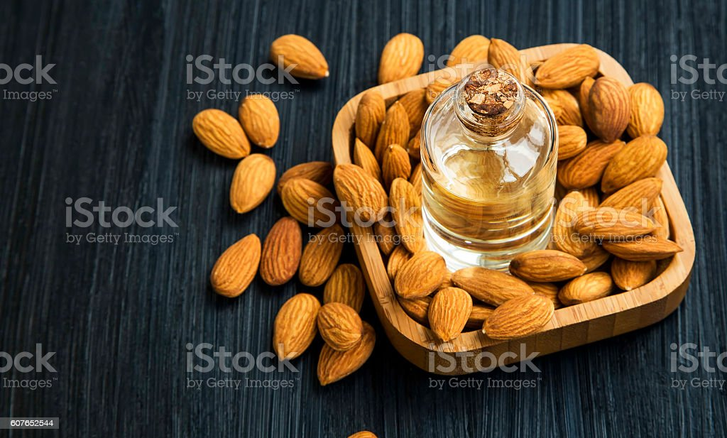 Healthy almonds oil bottle with almonds nuts in wooden bowl stock photo
