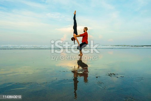 istock healthy and attractive fit couple of acrobats  doing acroyoga balance and meditation exercise on beautiful desert beach practicing balance and harmony posing in healthy lifestyle and yoga concept 1143840010