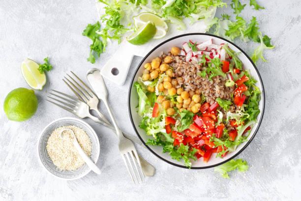 Gesunden und leckeren Schüssel mit Buchweizen und Salat aus Kichererbsen, frischem Pfeffer und Salat verlässt. Diätetische ausgewogene pflanzliche Lebensmittel. Vegane und vegetarische Teller. Ansicht von oben. Flach zu legen – Foto