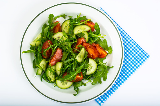 Healthy and diet food: arugula, cucumbers, tomatoes