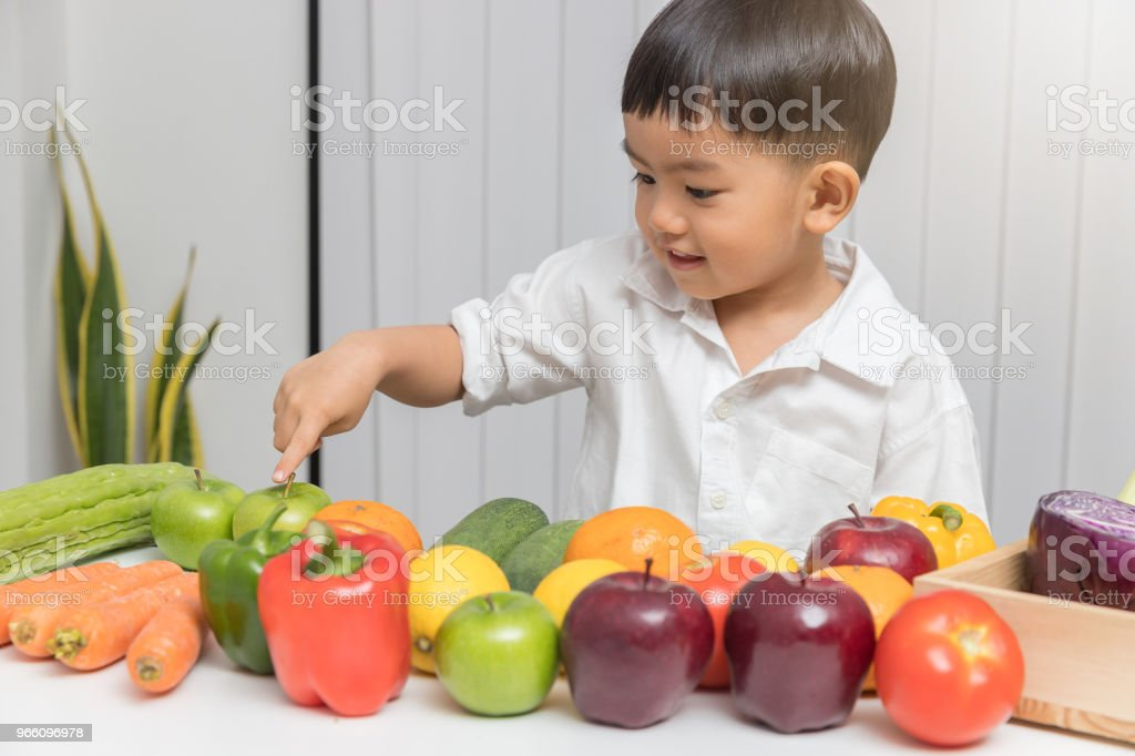 Healthy and nutrition concept. Kid learning about nutrition how to choose eating fresh fruits and vegetables. - Стоковые фото Азиатского и индийского происхождения роялти-фри