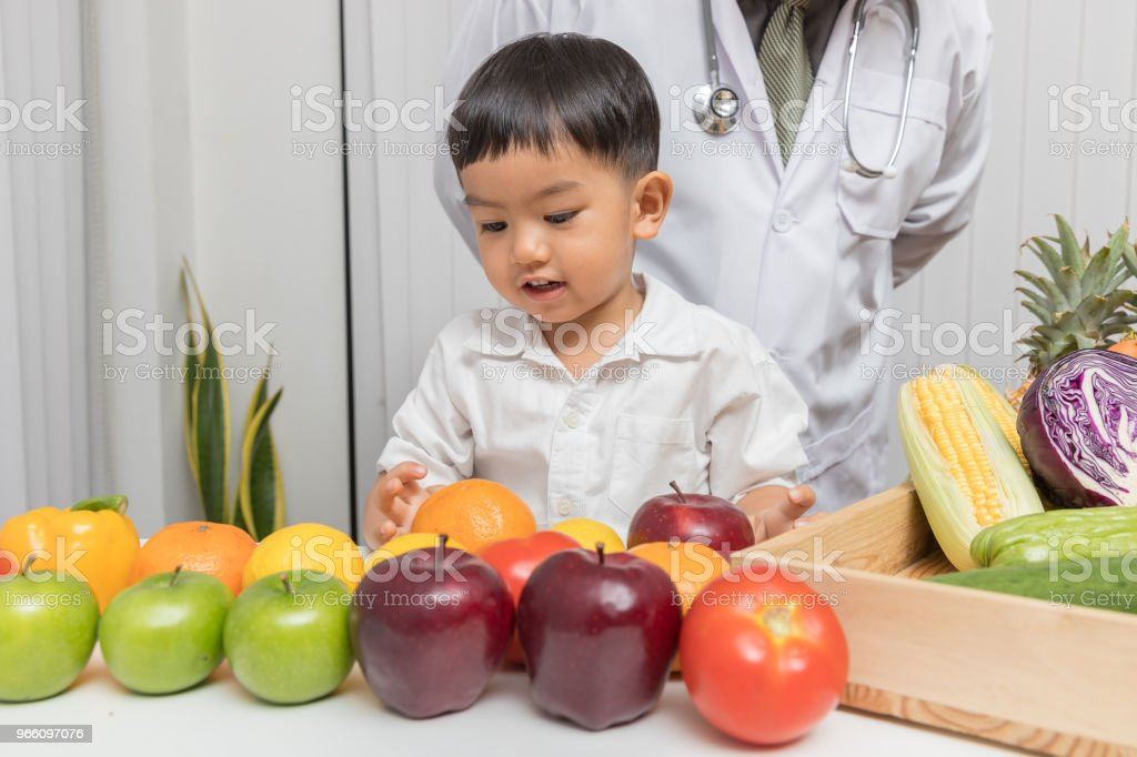 Healthy and nutrition concept. Kid learning about nutrition with doctor to choose eating fresh fruits and vegetables. - Royalty-free Apple - Fruit Stock Photo