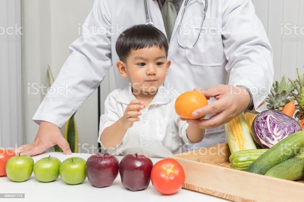Frisk och näring koncept. Kid lärande om näring med läkare att välja äta färsk frukt och grönsaker. - Royaltyfri Alternativ Bildbanksbilder