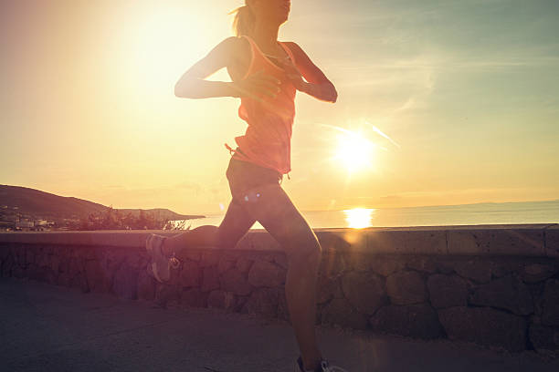 Healthy and sporty young woman running outdoors at sunset - foto de stock