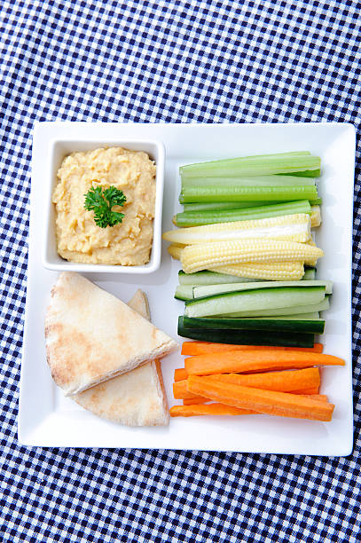 Healthy appetiser platter of hummus and raw vegetables stock photo