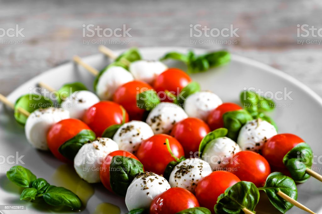 Healthy appetizer - caprese salad with tomato and mozzarella, italian food of mediterranean diet with olive oil dressing, weight loss concept stock photo