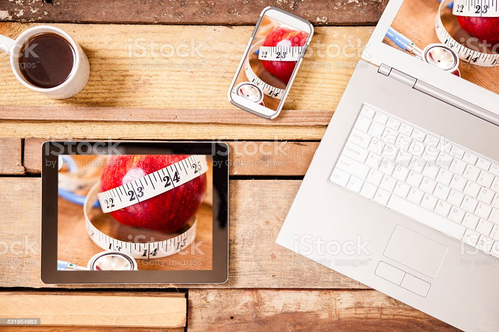 Healthy. Apple, stethoscope, tape measure. Digital tablet, laptop, phone screens. stock photo