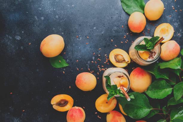 gesunde aprikose smoothies in glasflaschen - pfirsich milchshake stock-fotos und bilder