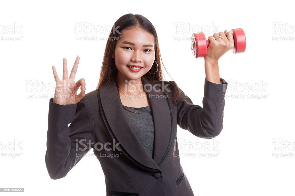 Healthy Asian business woman show OK with dumbbells. royalty-free stock photo