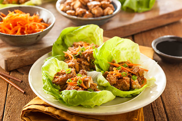 healthy asian chicken lettuce wrap - lettuce stock photos and pictures