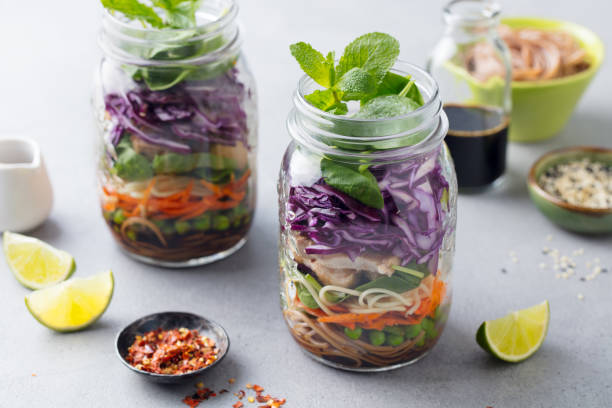 Healthy asian salad with noodles, vegetables, chicken and tofu in glass jars. Grey background. stock photo