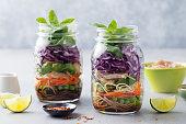 ガラス瓶に麺、野菜、鶏肉、豆腐を入れたヘルシーなアジアのサラダ。灰色の背景。