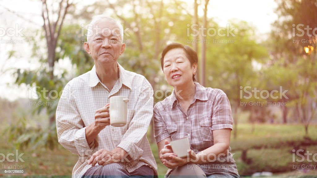 Healthy Asian senior couple drinking coffee in morning park together стоковое фото