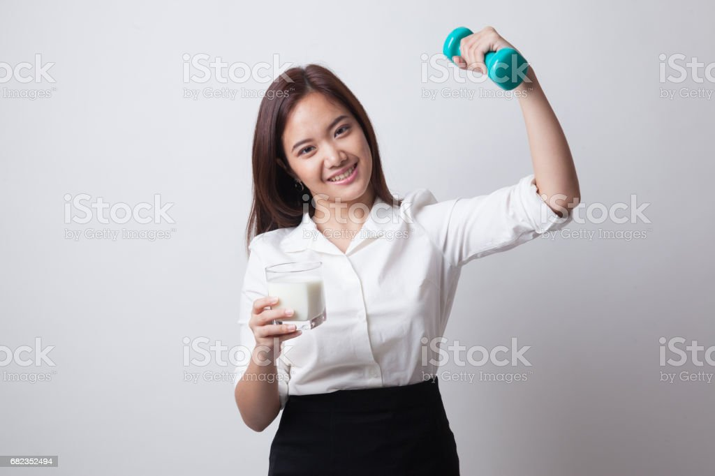 Healthy Asian woman drinking a glass of milk and dumbbell. foto stock royalty-free