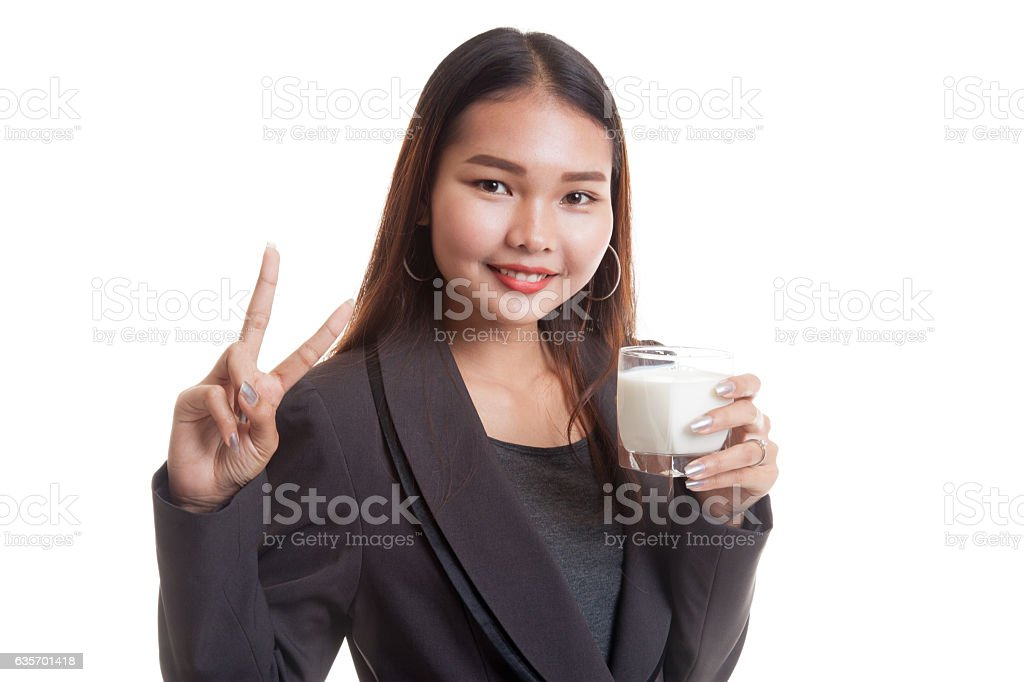 Healthy Asian woman drinking a glass of milk show victory royalty-free stock photo