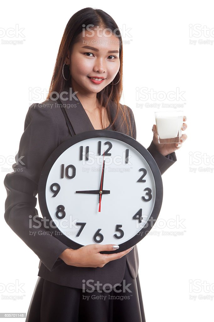 Healthy Asian woman drinking  glass of milk hold clock. royalty-free stock photo