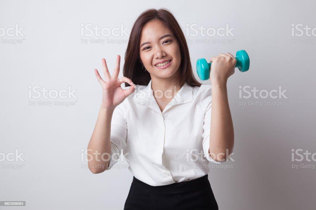 Healthy Asian woman show OK with dumbbells. zbiór zdjęć royalty-free