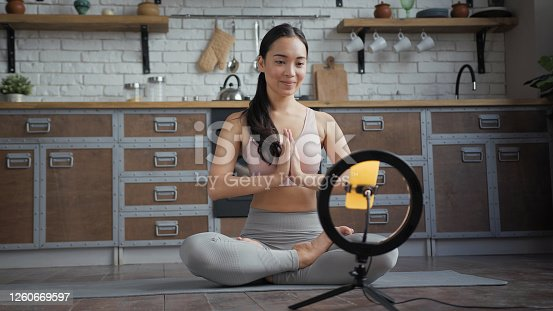 Healthy Asian yoga woman sitting in lotus position and doing online yoga lesson.