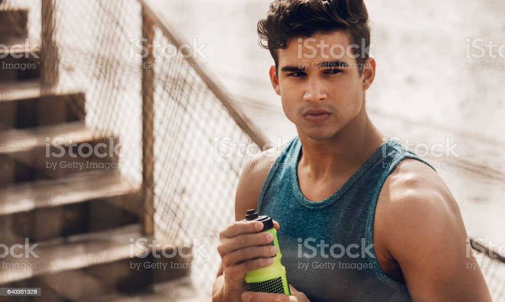 Healthy athletic man holding bottle of water stock photo