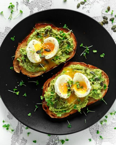 brindes de abacate e ovo saudáveis com sementes de abóbora e gergelim, polvilhadas com salada de agrião - torrada - fotografias e filmes do acervo