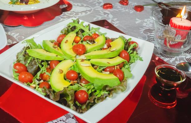 gesundes avocado gericht, kirschtomaten, mandeln salat und für romantische abendessen - englischer erbsen salat stock-fotos und bilder
