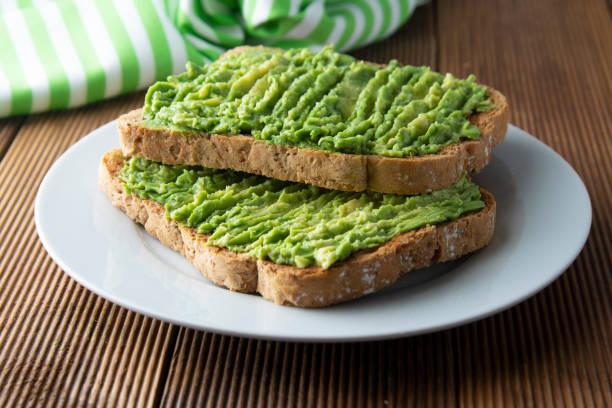sanduíche saudável do abacate, pão do brinde. pasta de abacate mushed, no fundo de madeira. guacamole. - abacate - fotografias e filmes do acervo